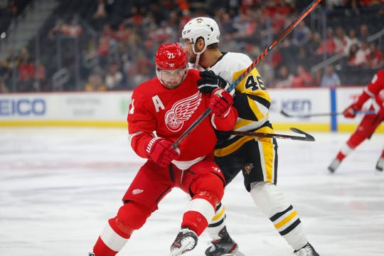 Pittsburgh Penguins center Zach Aston-Reese defends Red Wings center Dylan Larkin during a preseason game.