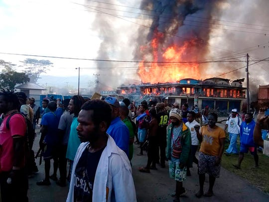 People gather as shops burn in the background during a protest in Wamena in Papua province, Indonesia, Monday, Sept 23, 2019.