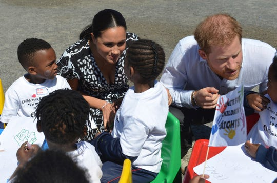 Britain's Prince Harry and Meghan Duchess of Sussex, greet children on their arrival at the Nyanga Methodist Church in Cape Town, South Africa.