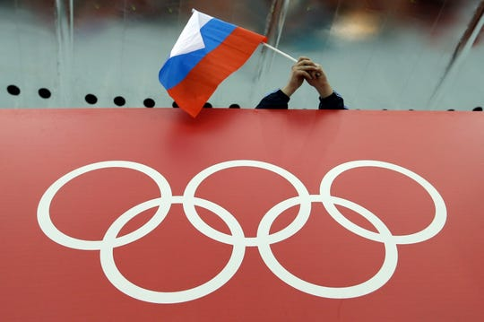 In this Feb. 18, 2014 file photo, a Russian skating fan holds the country's national flag over the Olympic rings before the men's 10,000-meter speedskating race at Adler Arena Skating Center during the Winter Olympics in Sochi, Russia.