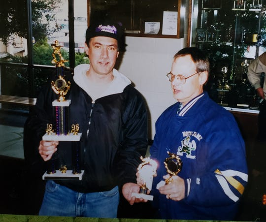 Mike Hoon Sr. (left) poses with a championship trophy the Evansville Thunder won in 1998.