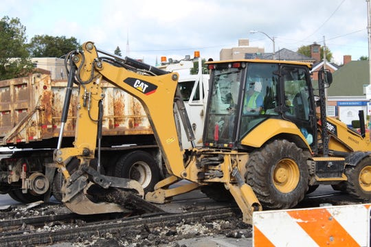 Crews remove Norfolk Southern railroad tracks Monday at the State Street Bridge.