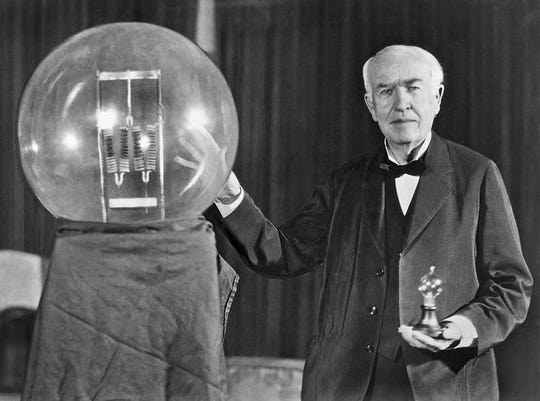 Inventor Thomas Edison poses in 1929 with a replica of his first  successful incandescent lamp. The photo was taken during an anniversary banquet in his honor in Orange, New Jersey.