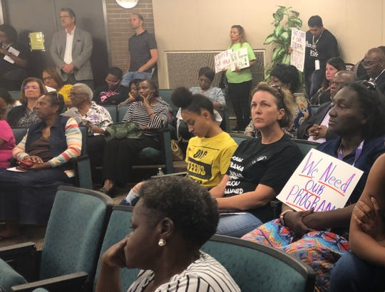 Audience members watch speakers address Fort Myers city council about the plan to cut city funding to local community organizations and nonprofits.