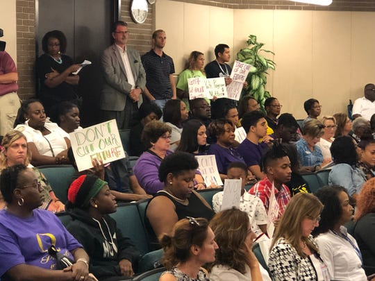 Audience members hold signs protesting the Fort Myers' city council decision to cut funding to 26 local organizations for the next budget.