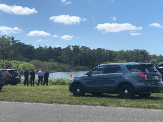 Divers with the Lee County Sheriff's Office are searching a body of water near the intersection of Forum Boulevard and Warrior Way. More than a dozen emergency vehicles, including LCSO and the Fort Myers Police Department, are parked within the apparent crime scene.