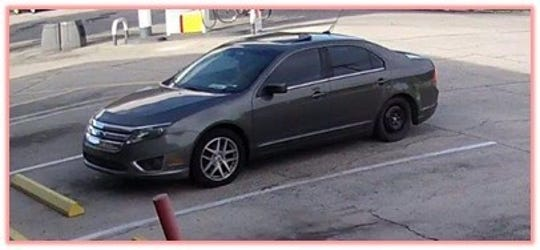 The two male subjects and a female subject may be driving a 2011 Ford Fusion with a Georgia tag.