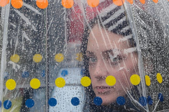Britny Orr of Pewaukee looks out from beneath her umbrella before the football game between the Green Bay Packers and Denver Broncos on Sunday, Sept. 22, 2019, at Lambeau Field in Green Bay, Wis.