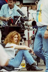 Julia Roberts sits during a break filming Sleeping With the Enemy in Abbeville, South Carolina in August 1990, a scene of a parade through the downtown street. Roberts, who grew up in nearby Smyrna, Georgia just a few years earlier, landed several big roles in Hollywood movies before and after this one about a woman escaping an abusive husband.