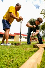 Yeoman Second Class Christian Price (left), from Waldorf, Md., and Torpedoman Second Class Curtis Branz, from Osburn, Idaho, both assigned to Commander, Submarine Squadron Fifteen, shovel dirt into a wheelbarrow during a community relations project at the Infant of Prague Catholic Nursery and Kindergarten. Nine sailors assigned to CSS-15 built a swing set for the school's playground