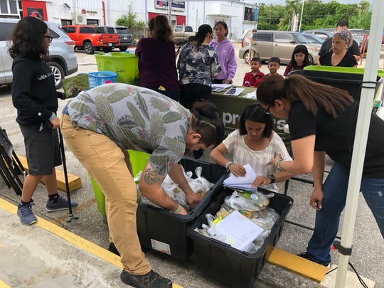 Loco Promos owner Jennifer Rodriguez, right, and store helpers sort through pre-order packages in search of a customer's order of insect repellent products in Harmon on Monday, Sept. 23, 2019.