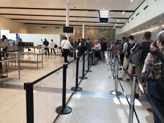 Passengers wait to go through security at the Indianapolis International Airport on Monday, Sept. 23, 2019.