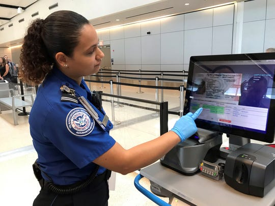 TSA officer Sharleen Rivera shows the verification system for reading driver's licenses and identification cards in order to travel.