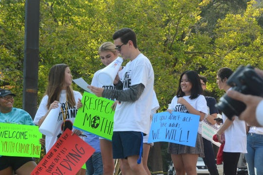 A group of young demonstrators speak and hold signs at a climate change rally at the state Capitol on Sept. 20, 2019. The rally was held three days before a Climate Action Summit was held at the United Nations Headquarters in New York.