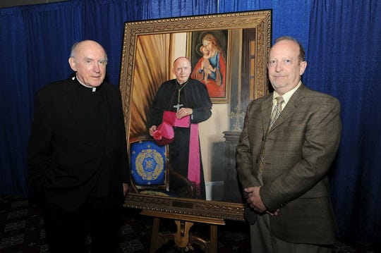 In this file photo, Dr. Ken LeBlanc, right, hand painted this portrait of Archbishop Harry Flynn. The portrait will hang in Flynn Hall at the University of St. Thomas.