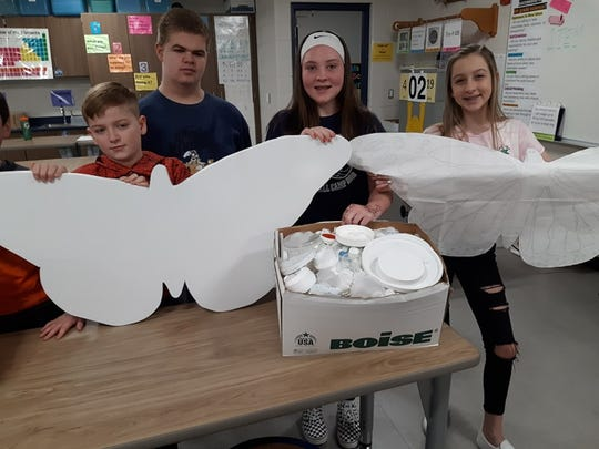 DeWitt Middle School students show their work in progress on an upclyced butterfly sculpture from spring 2019. The sculpture was found vandalized Sept. 29, 2019.