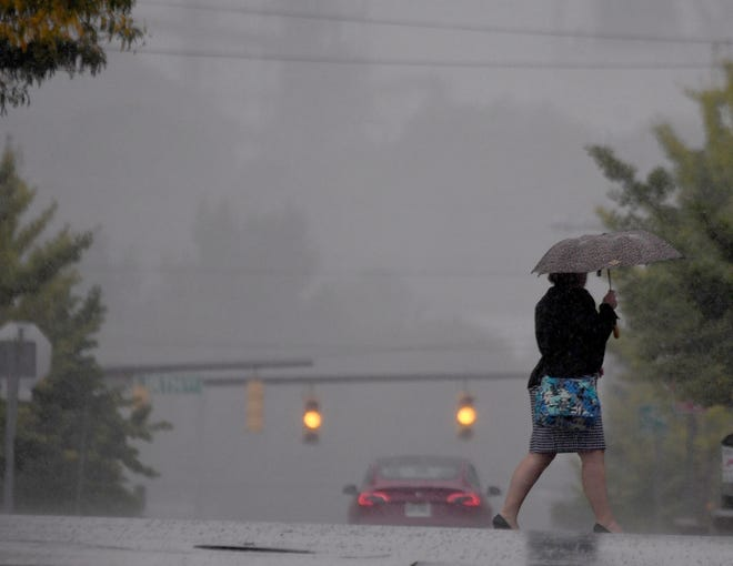 A pedestrian in Mansfield uses an umbrella to stay dry on her morning commute Monday, the first day of fall, which officially began at 3:50 a.m. Tuesday's forecast calls for lots of sunshine and afternoon temperatures in the lower 70s.