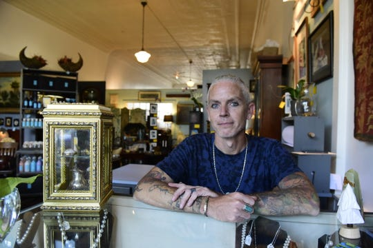 Lucas Hargis sits behind the front counter of the new Lucah Designs store in downtown Mansfield.