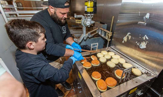 Ten-year-old beekeeper Miles Bergner of Wauwatosa learns the art of doughnut making from Joey Carioti, co-owner of Cranky Al's in Wauwatosa.