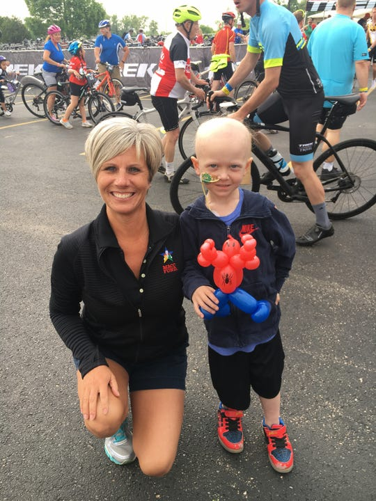 Becky Pinter, left, president and chief executive officer of the MACC Fund, meets a young patient during the TREK 100 Ride for Hope.