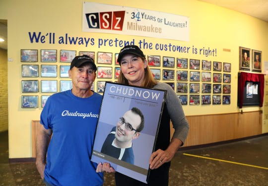 Dick Chudnow, left, and his wife Jennifer Rupp hold a framed photo of their son Nick at ComedySportz Milwaukee. They lost their only son Nick to a fentanyl overdose at age 29.  They have started a charity to raise money to support efforts to prevent drug abuse by kids.  The portrait of Nick and other performers line the walls are by house photographer Michele Kieweg.