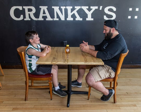 Ten-year-old beekeeper Miles Bergner of Wauwatosa talks with Joey Carioti, co-owner of Cranky Al's doughnut, coffee and pizza shop, regarding a business venture to create honey doughnuts at the Wauwatosa restaurant.