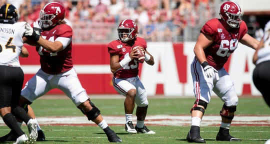 Alabama quarterback Tua Tagovailoa (13) passes from behind Alabama offensive linemen Jedrick Wills, Jr., (74) and Landon Dickerson (69) against Southern Miss at Bryant-Denny Stadium in Tuscaloosa, Ala., on Saturday September 21, 2019.