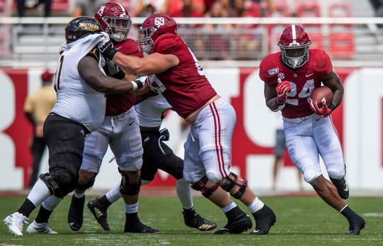 Alabama running back Brian Robinson, Jr., (24) carries behind the blocking of Alabama offensive linemen Landon Dickerson (69) and Jedrick Wills, Jr., (74) against Southern Miss at Bryant-Denny Stadium in Tuscaloosa, Ala., on Saturday September 21, 2019.