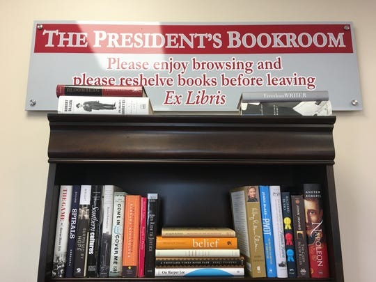 A sign stands over a bookshelf inside the Scarlet and Grey shop at 1140 E. Fairview Ave.