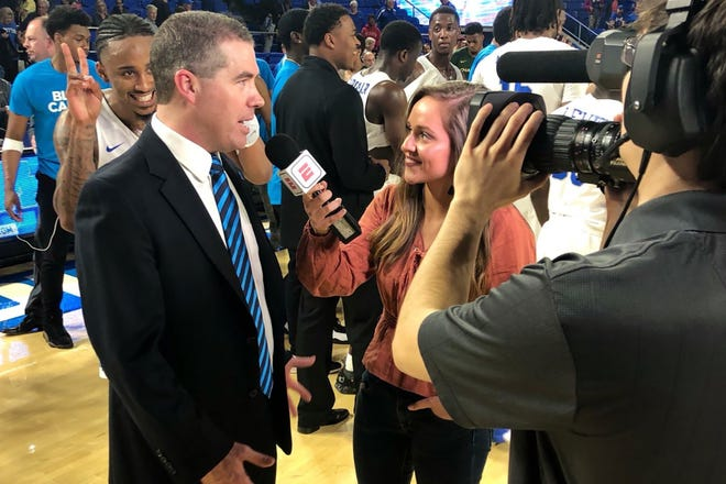 MTSU College of Media and Entertainment senior Kaitlyn Runion interviews MTSU men's basketball coach Nick McDevitt following a game at Murphy Center. Runion has had opportunities to be a sideline reporter for ESPN+ broadcasts of MTSU men's and women's basketball games.