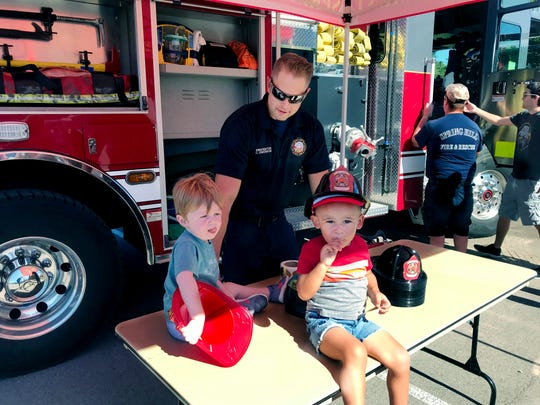 Beck Tefel (left) and Ezra Elmore get fire hats from Spring Hill fireman at at  the 2018 Touch-a-Truck event