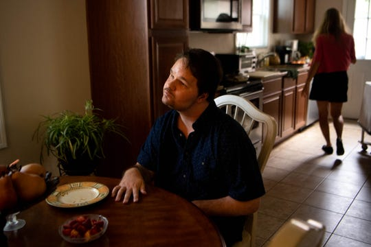 Luke Putney sits at the table as his mother, Nancy Hoddinott, goes into the kitchen at his home Monday, Sept. 23, 2019, in Nashville, Tenn. Putney has been blind since he was a teen, but kept playing music until a stroke and seizure, after brain surgery to remove a tumor, left him unable to do so. Two years later, he is making great strides in his recovery.