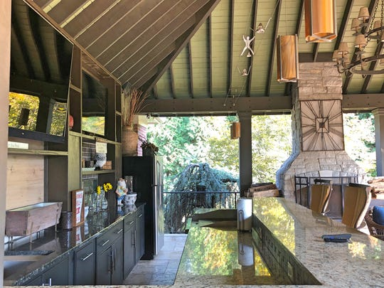 This is Lee and Alecia Seelig's outdoor kitchen and bar. This section of the patio has two televisions for watching multiple football games at once. The fireplace enables the family to use the outdoor space even in colder months. The porch also has a third TV at the other end for anyone not wanting to watch the game.