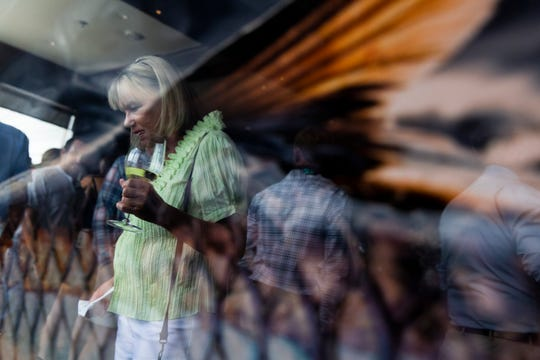 Mary Kephart is reflected on a fish print during a fundraiser at The Bay House in Naples on Sunday, September 22, 2019.