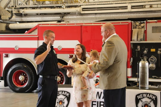 Jesse Myers (left) raises his hand on Monday, Sept. 23, 2019, to be sworn in as Newark Fire Department's newest firefighter/paramedic as Newark Safety Director Steve Baum reads the oath, and Myers' wife, Ashley, and daughter, Leah, look on. Myers started in fire service through Mary Ann Township as a volunteer, wanting to help the community in which he lived. A 2005 Licking Valley graduate, Myers attended CTEC and COTC and has served on departments in Mary Ann Township and Hebron.