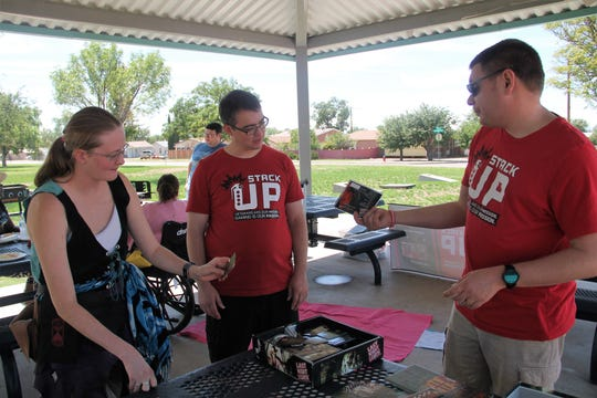 """From left Kenya Robinette, Daniel McArdle and Theodore Wiseman set up a game of """"Last Night on Earth: The Zombie Game."""" The Stack Up! Alamogordo group held one its periodic meet-ups at Kids Kingdom Sunday, Sept. 23. The event was a barbecue and games including role playing and yard games."""