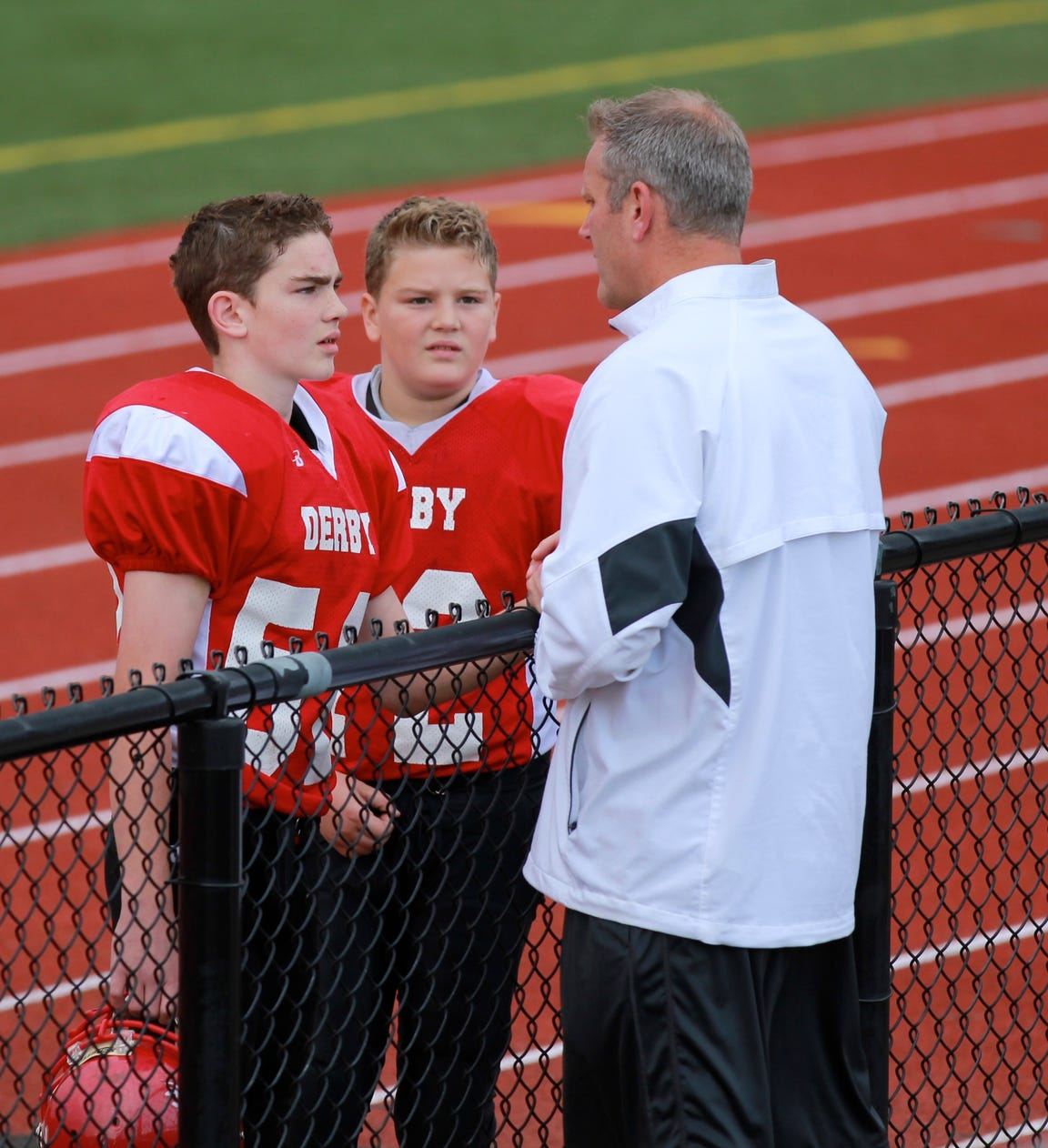 Caden and James DeWald talk to their father Jim on the sideline of a football game.