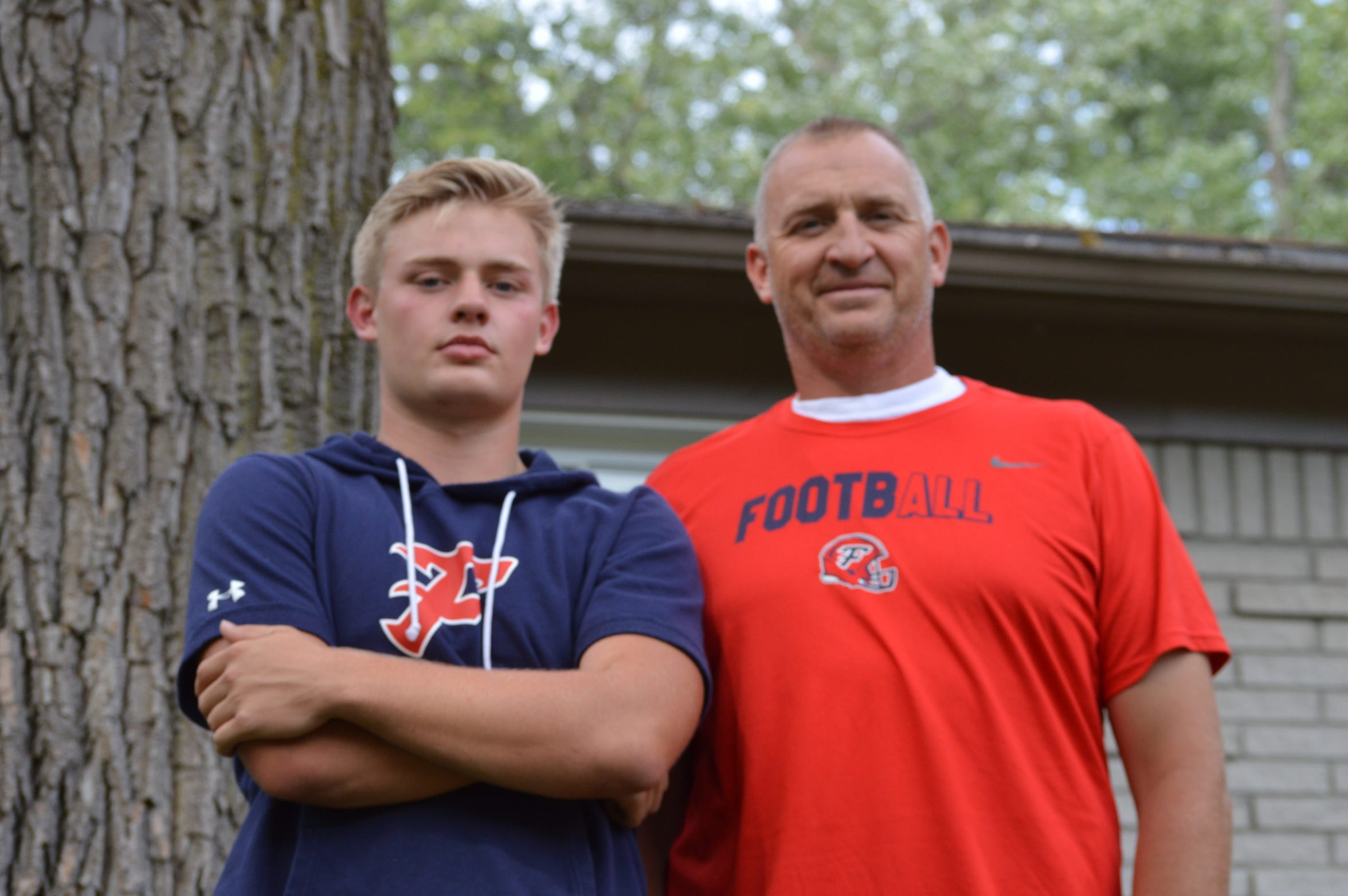 Livonia Franklin quarterback Jake Kelbert stands with his father and head coach Chris Kelbert