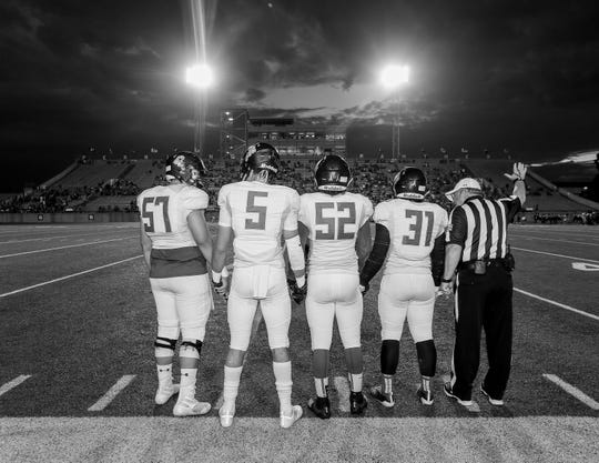 """(From left to right) Daryne Murillo, Cole Martello, Andrew Gonzalez and Derrick Pine line up with the referee before Friday night's football game against Permian High in Odessa, Texas, on Sept. 20, 2019 in a similar fashion to the movie poster for """"Friday Night Lights."""""""