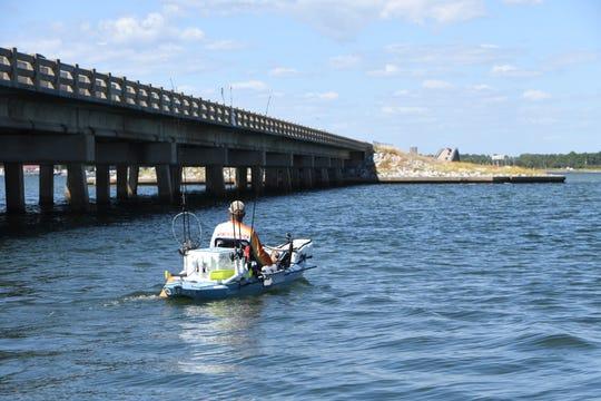 Fisherman Joseph Rizzo paddles his kayak along the causeway in Navarre on Monday.