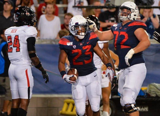 Arizona running back Gary Brightwell (23) and offensive lineman Edgar Burrola (72) celebrate during the second half of a game against Texas Tech on Sept. 14 at Arizona Stadium.