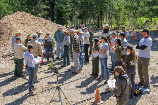 About two dozen National Park Service employees gather for a morning briefing about a plan to move 31 bison from the area outside Grand Canyon National Park to Oklahoma.