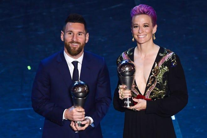 Lionel Messi y Megan Rapinoe posan con sus respectivas estatuillas.