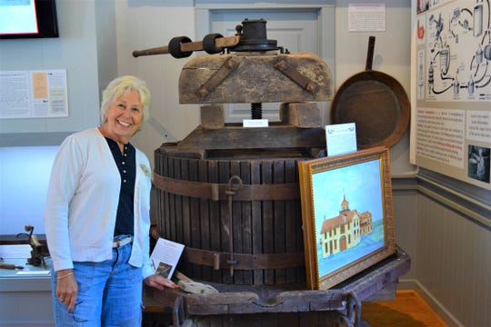Curator Jane Spriestersbach stands beside a vintage grape press that once extracted juice to make wine on the island.