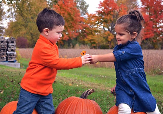 Kids pass each other a flower at the CornFun Corn Maze Adventure And Pumpkin Patch in Casco.