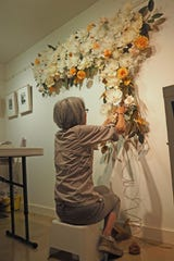 """Co-curator Mary Untalan creates paper art for the """"Paper, Process, Possibilities"""" exhibit opening at Tivoli Artists Gallery."""