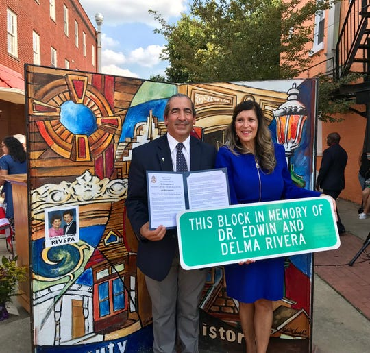 Eddie and Delma River, children of the late Dr. Edwin and Delma Rivera, show off a sign dedicating the 200 block of East Princess Street in York in honor of the two Hispanic community leaders on Sunday.