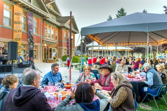Guests enjoy a ravioli dinner at the Taste of the Valley Festival outside the Jeanne Dini Cultural Center.