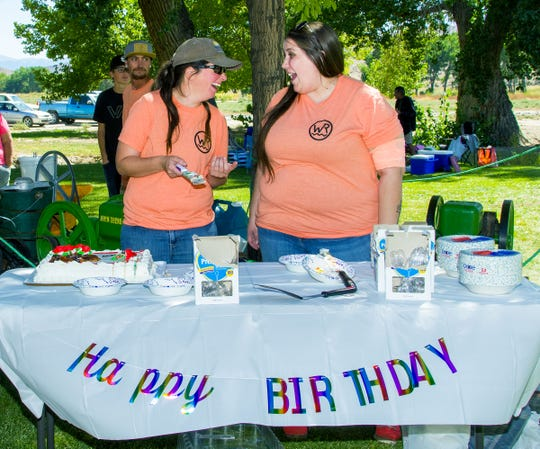 Samantha Essig, left, a park conservation specialist, and Raychael Valente, a park administrative assistant, serve the last of four cakes celebrating the Walker River Recreation Area's first year.