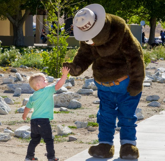 A toddler gives Smokey Bear a high-five during birthday festivities at the Walker River Recreation Area on Saturday. Smokey celebrated his 75th birthday on Aug. 9.